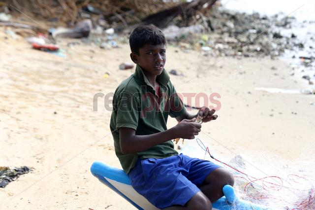 Sri Lankan boy fixing a fishing net