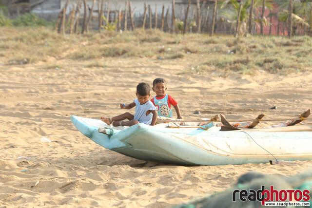 Little kids playing on a canoe, Sri Lanka