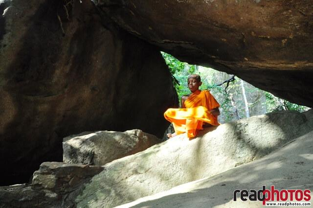 Little monk meditating in a cave, Sri Lanka