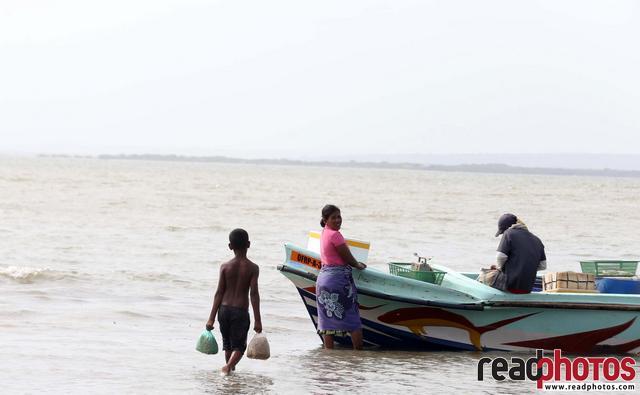 Young boy carries flood rations, Sri Lanka - Read Photos