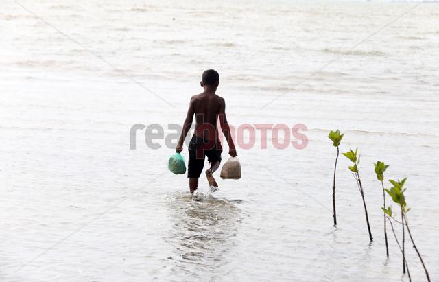 Sri Lankan young boy carry rations during flood times