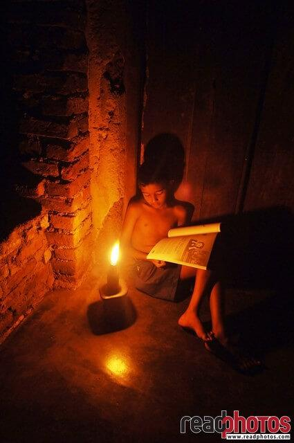 Small boy studying with a oil lamp, Sri Lanka