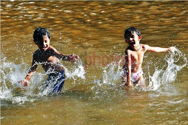 Two brothers playing in the water, Sri Lanka