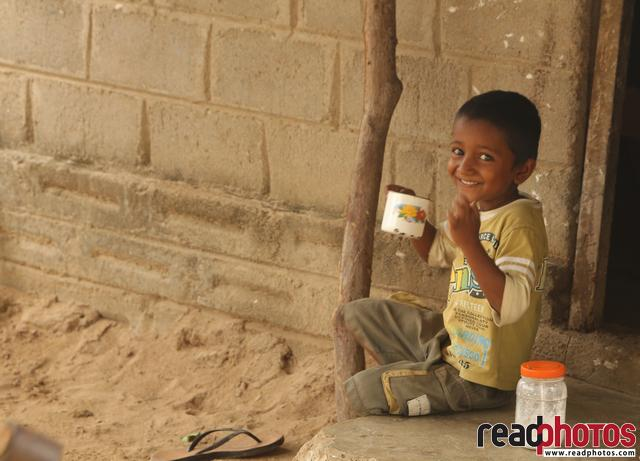 Smiling little boy having tea, Sri Lanka